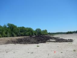 Start of construction, trucks start pulling sediment from the lake.