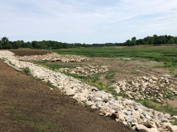 riprap placed along Evergreen Ave. Rock piles for fish habitat also pictured, Summer 2018